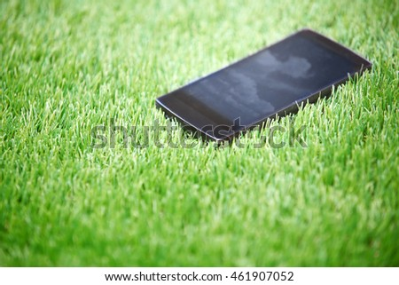 Smartphone lost in the grass. Horizontal photo