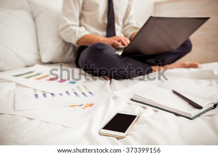 Smartphone, notebook and documents on bed, in the background young businessman in white classical shirt and dark tie working and using laptop while sitting cross-legged on bed, close-up - stock photo