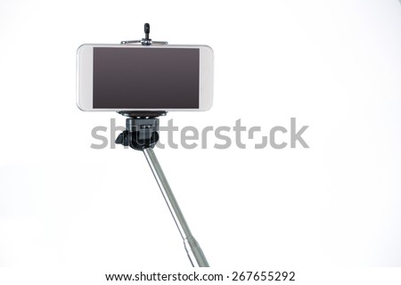 Smartphone on a selfie stick shot in studio - stock photo