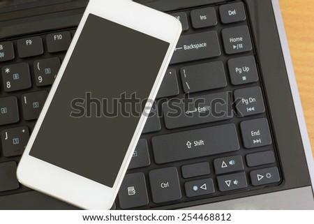 smartphone on laptop computer keyboard - stock photo