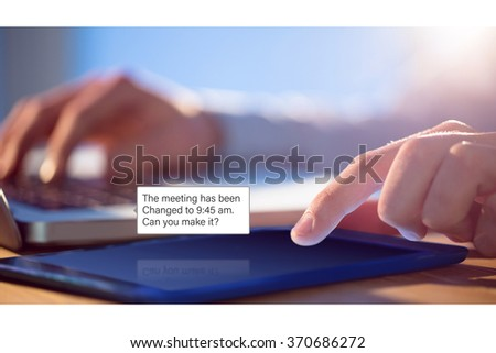 Smartphone text messaging against businessman using laptop and tablet at desk - stock photo