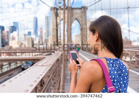 Smartphone texting girl on Brooklyn bridge in urban New York City, Manhattan USA. View from the back of unrecognizable business woman holding phone reading or using social media in summer. - stock photo