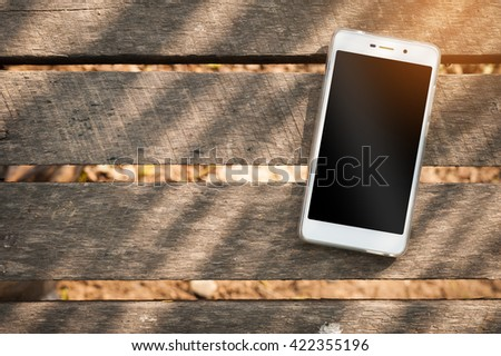 Smartphone with blank area on touch screen on rustic wood table at outdoor area in morning time with high contrast natural lighting - stock photo