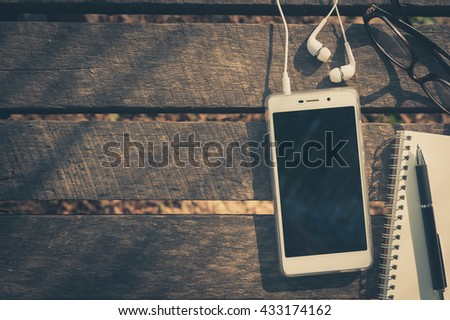 Smartphone with blank area on touchscreen with in ear headset, opened notebook, pen, and glasses on rustic wood table in morning time with vintage filter effect - stock photo