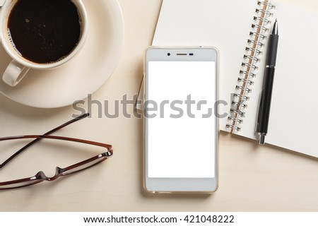Smartphone with blank area on touchscreen with notebook, pen, glasses, and coffee cup on wood table - stock photo