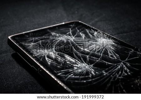 Smartphone with broken screen on dark background - stock photo