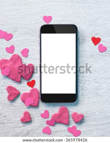 Smartphone with heap of small hearts on white wooden background. Valentines Day concept - stock photo