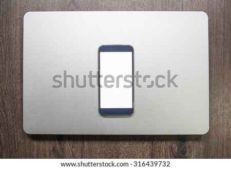 Smartphone with isolated screen on laptop on old wooden desk. Mock up - stock photo