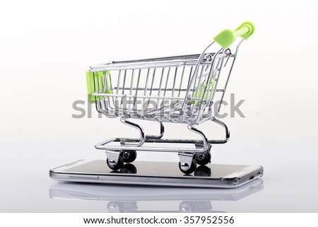 Smartphone with shopping cart on white background - stock photo