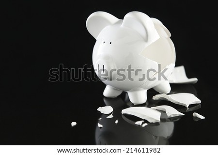 Smashed white ceramic piggy bank on a black background with copyspace conceptual of raiding ones savings in time of financial crisis - stock photo
