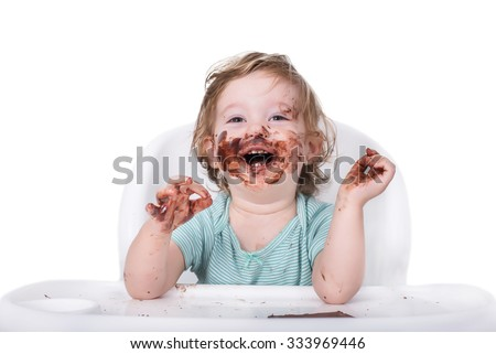 Smeared baby eating chocolate for the first time - stock photo