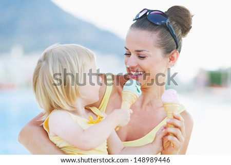 Smeared mother and baby eating ice cream - stock photo