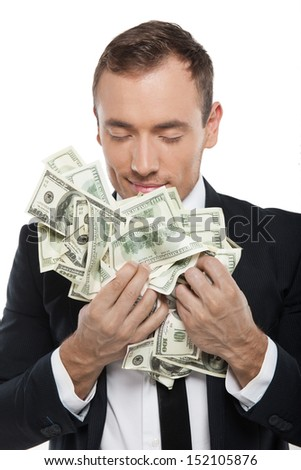 Smelling money. Happy young businessman in formalwear smelling money while sisolated on white