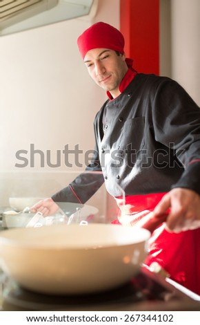Smells good. Young male cook finishing a meal in a commercial kitchen, - stock photo