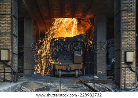 Smelting metal in a metallurgical plant. Liquid iron from the ladle - stock photo