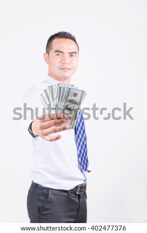 Smile asian business man showing money dollar, shallow depth of field, selective focus on money - stock photo