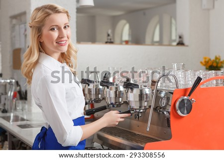 Smile at camera. Portrait of young beautiful smiling blond-haired woman standing near coffee machine in cafe - stock photo