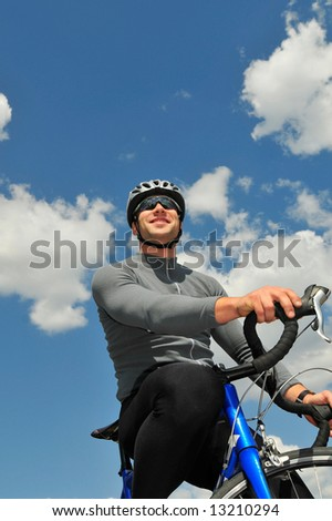 Smile bicyclist on a background of the blue sky - stock photo
