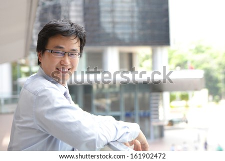 Smile business man with office building background, asian male