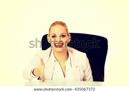 Smile business woman sitting behind the desk with an open hand ready for handshake - stock photo