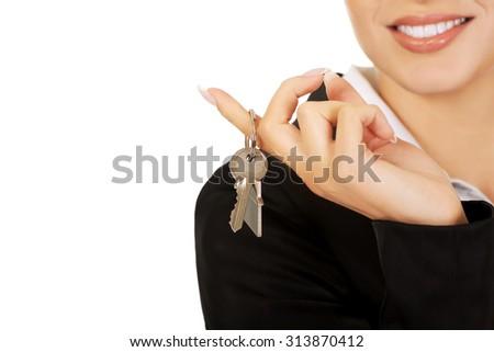 Smile businesswoman real estate agent giving keys. - stock photo