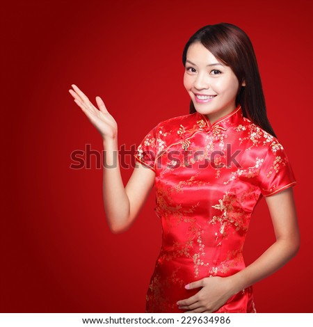 Smile Chinese woman dress traditional cheongsam and introduce on red background. asian beauty - stock photo
