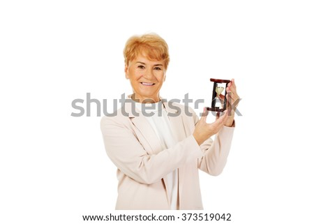 Smile elderly  business woman holding sandglass - stock photo