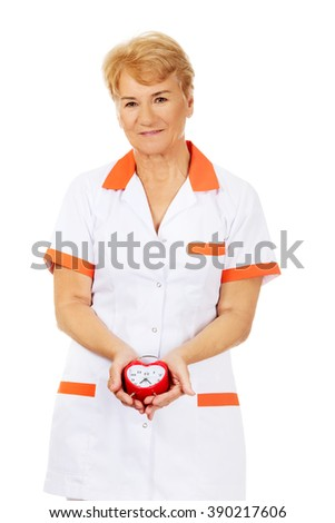 Smile elderly female doctor or nurse holds alarm clock - stock photo