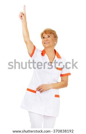 Smile elderly female doctor or nurse pointing up - stock photo