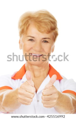 Smile elderly female doctor or nurse shows thumbs up - stock photo