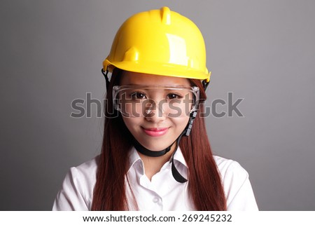 Smile engineer woman isolated on gray background. asian - stock photo