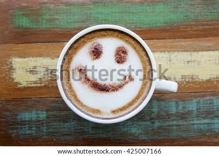 Smile face drawing on latte art coffee , wood color background - stock photo