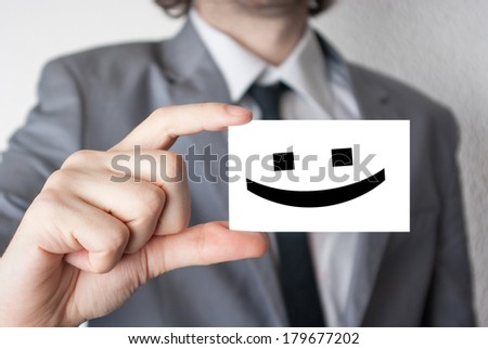 Smile happy face. Businessman in suit with a black tie showing or holding business card