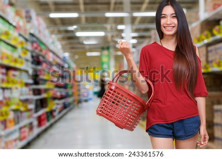 smile lady holding shopping basket in supermarket - stock photo