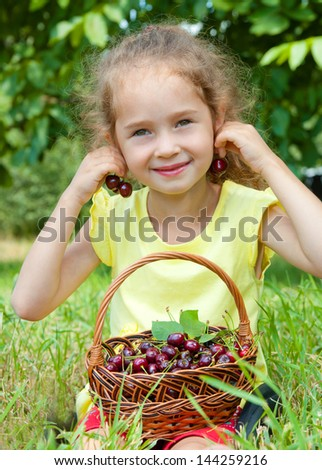 Smile little girl in summer day with a basket of cherries on the grass