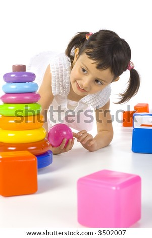 Smile, little girl kneeling between colored rings and blocks. White background - stock photo