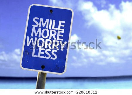 Smile More Worry Less sign with a beach on background
