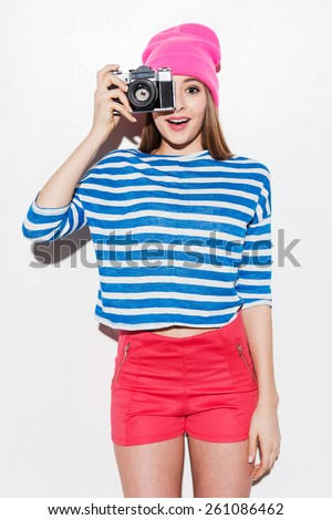 Smile! Playful young woman in funky clothes looking through a camera while standing against white background - stock photo