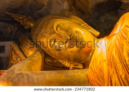 Smile reclining buddha statue in nirvana position at Khaoluang Cave, Phetchaburi, Thailand - stock photo