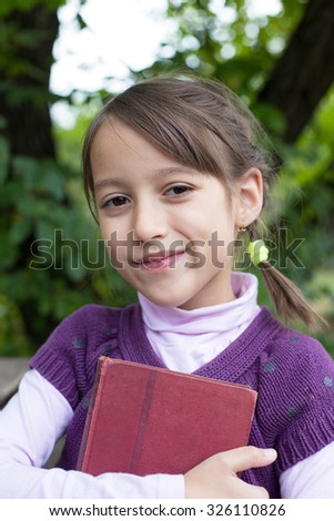 smile school girl holding an old book