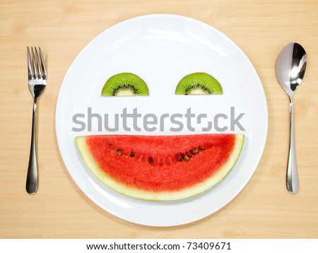 Smile watermelon and kiwi served on white plate - stock photo