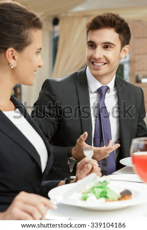 Smile works for business too. Vertical half length portrait of a young businessman talking to his colleague over lunch and smiling - stock photo