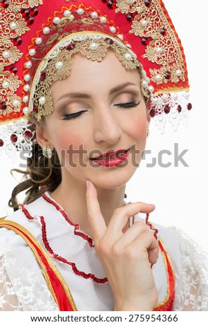 Smile young woman hands on hips portrait in russian traditional costume -- red sarafan and kokoshnik. Studio shot isolated on white.