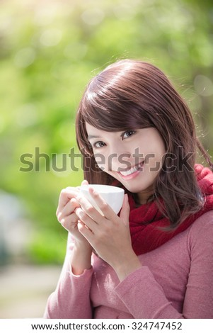 smile young woman holding cup of coffee or tea and wearing winter clothing with green background, asian beauty