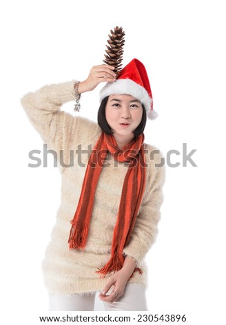 Smile young woman in red wearing santa hat holding Pine cone - stock photo