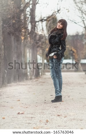 Smile young woman posing outdoors. Attractive girl standing and wearing fur,  autmn day - stock photo