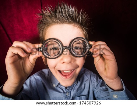 Smiled child with big glasses. Red curtain background - stock photo