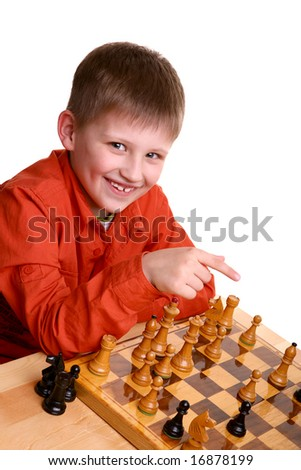 Smiled little blond boy in orange shirt pointing with finger while playing chess game - stock photo