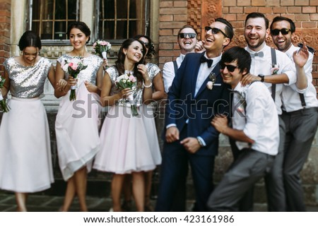 Smiles of the groom with bridesmaids and groomsmen