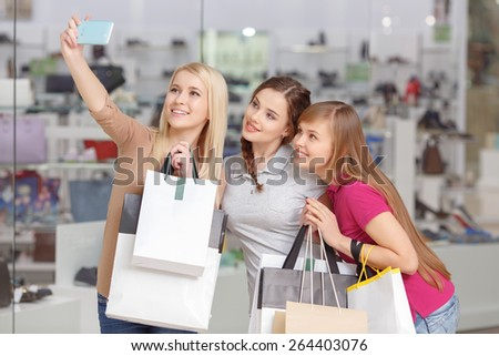 Smiley and cheerful shoppers.  Beautiful and young girl teenagers in casual clothes holding bags and making selfie in the shopping mall - stock photo
